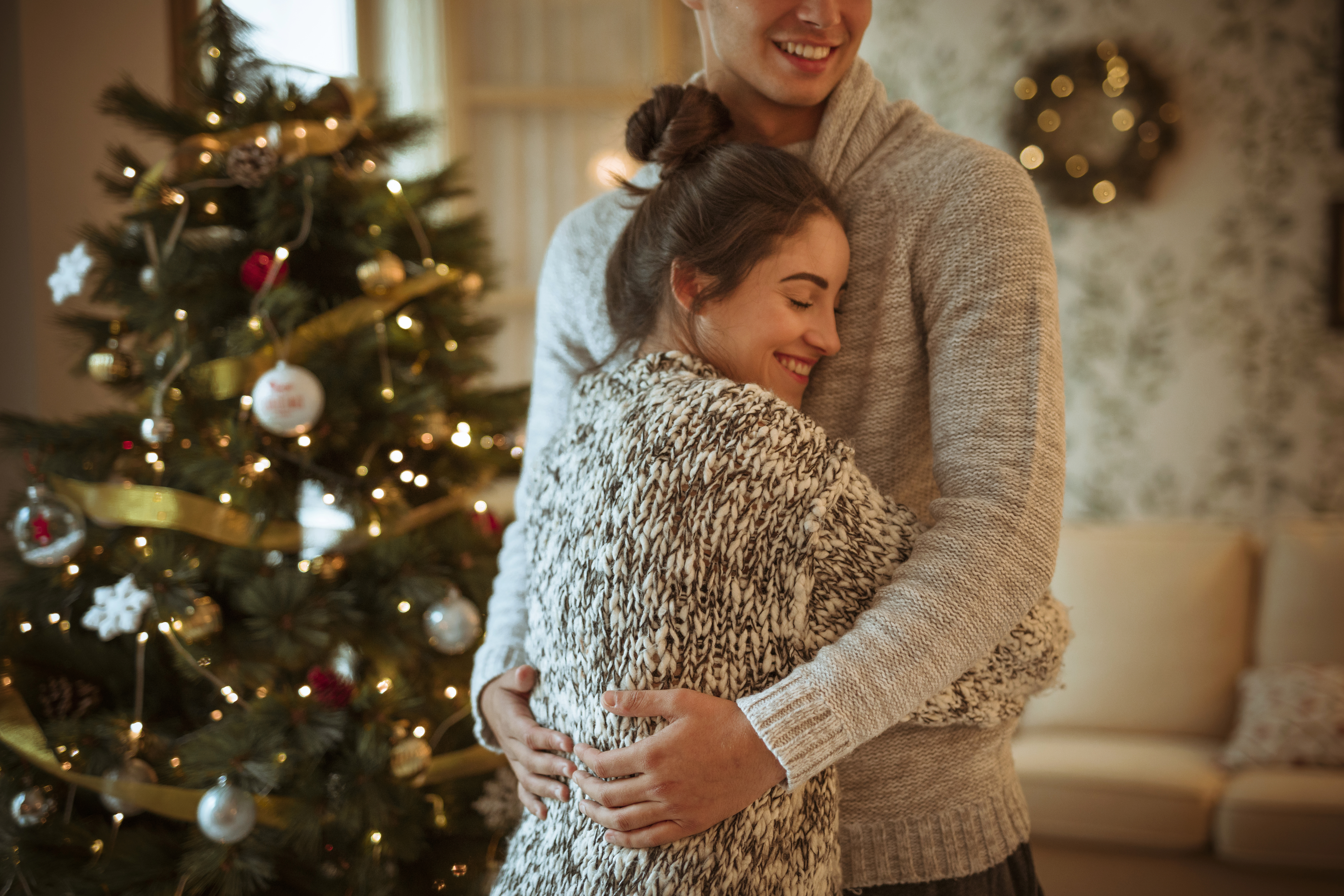 young-woman-hugging-man-near-decorated-fir-tree