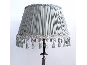 Stojací lampa s modrošedým stínidlem a třásněmi na podstavci s bronzovou patinou