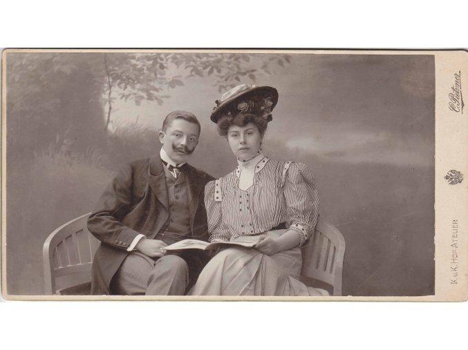 Mladý pár s knihou na lavičce