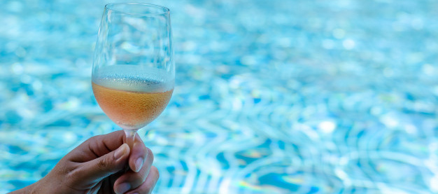hand-toasting-with-glasses-rose-wine-swimming-pool_74663-115