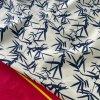 Strečová bavlna značky Violanti se vzorem větviček s červenou bordurou