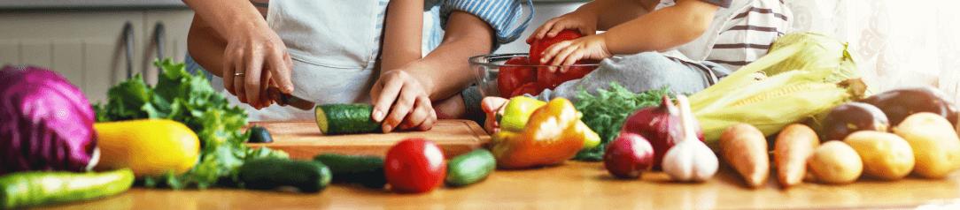 krájení okurky na stole plném zeleniny