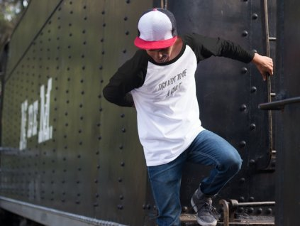 5717 guy wearing a cap and raglan 3 4 sleeve t shirt mockup jumping from a train a12492