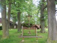 Kamenný kříž na konci vsi obklopený čtyřmi lípami