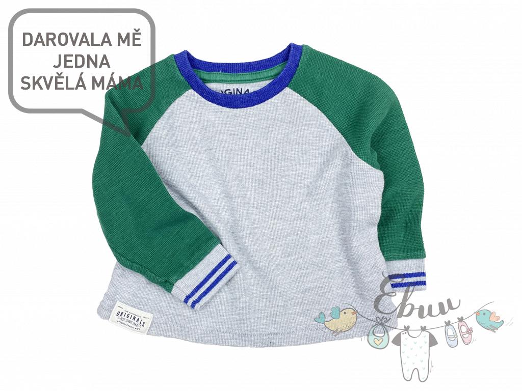 šedý svetr se zelenými rukávy