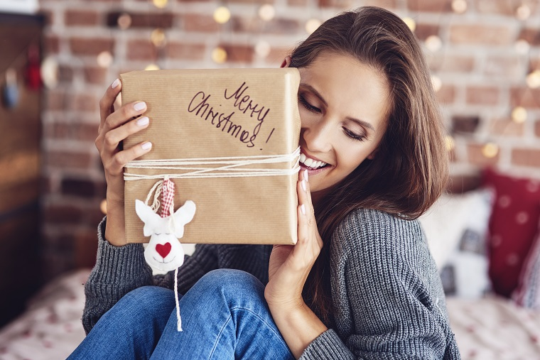 cheerful-woman-sitting-on-bed-and-holding-a-gift-SLWTFJX