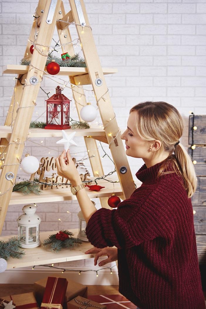 young-woman-decorating-the-christmas-tree-GDUKA7C