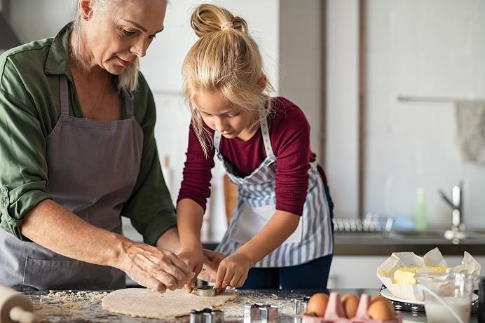 girl-with-grandmother-preparing-cookies-7CN4Y9R