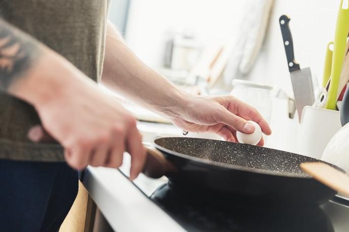 man-preparing-fried-eggs-in-the-kitchen-P3QE5HN