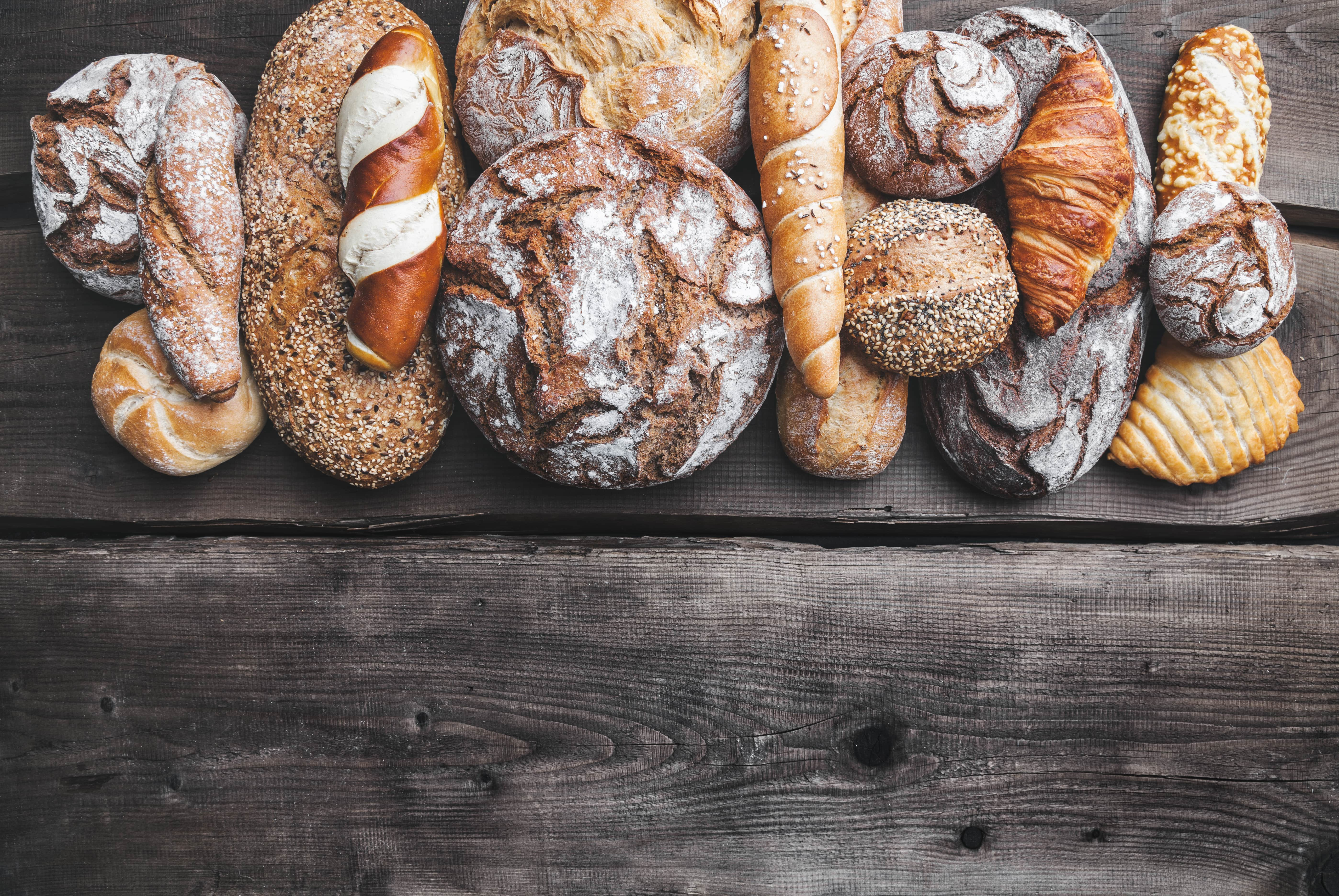 delicious-fresh-bread-on-wooden-background-P9FSLCH-min