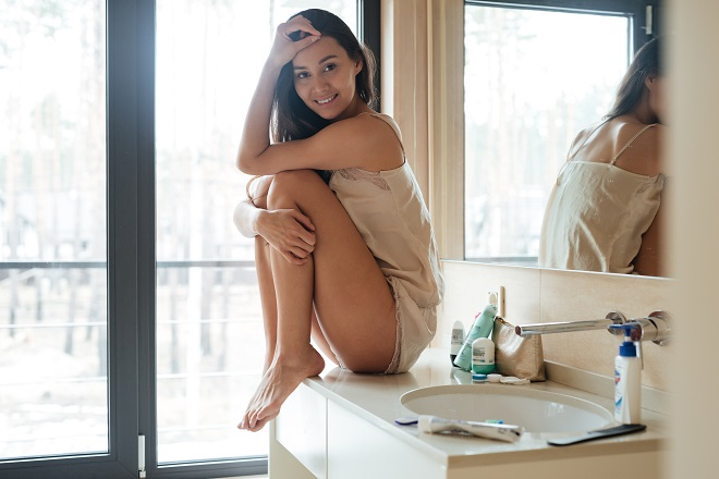 smiling-gorgeous-young-woman-sitting-in-bathroom-PME24UK