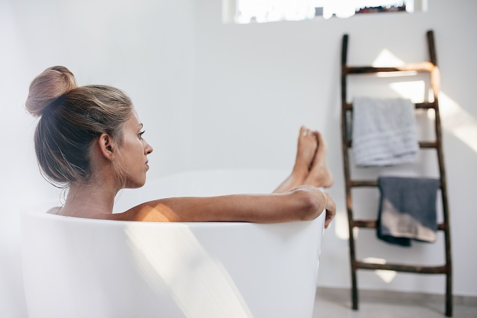young-woman-lying-in-bathtub-and-looking-away-PQ5VNTV