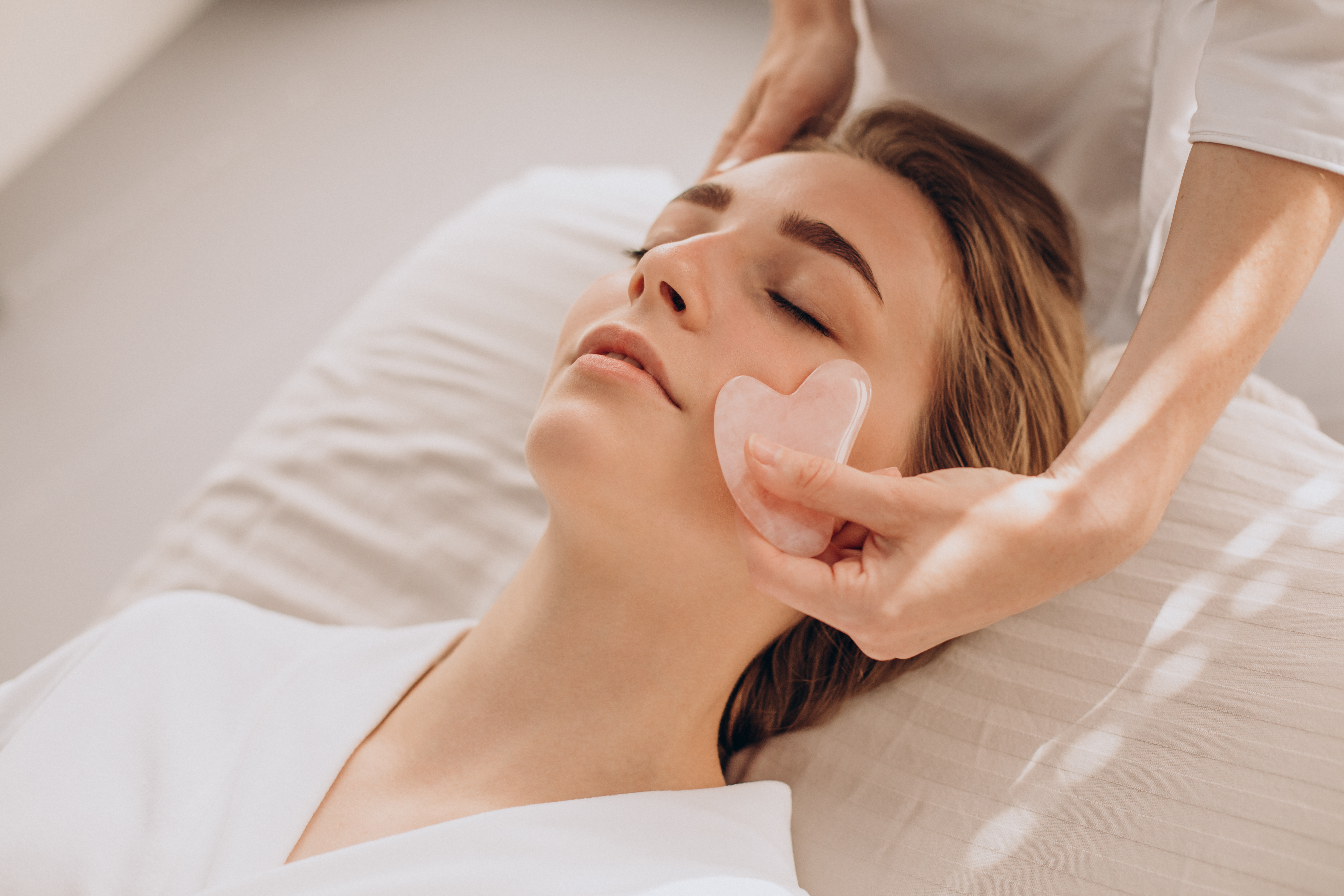 woman-salon-making-beauty-treatment-with-gua-sha-stone