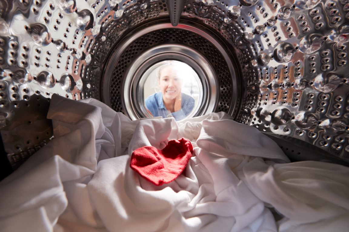 woman-looking-inside-washing-machine-with-red-sock-F82LP93