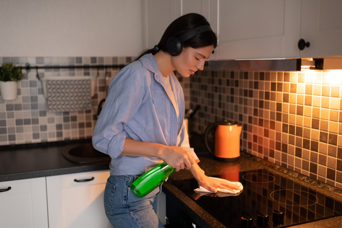 woman-with-headphones-cleaning-stove-in-kitchen-S3V3V4K