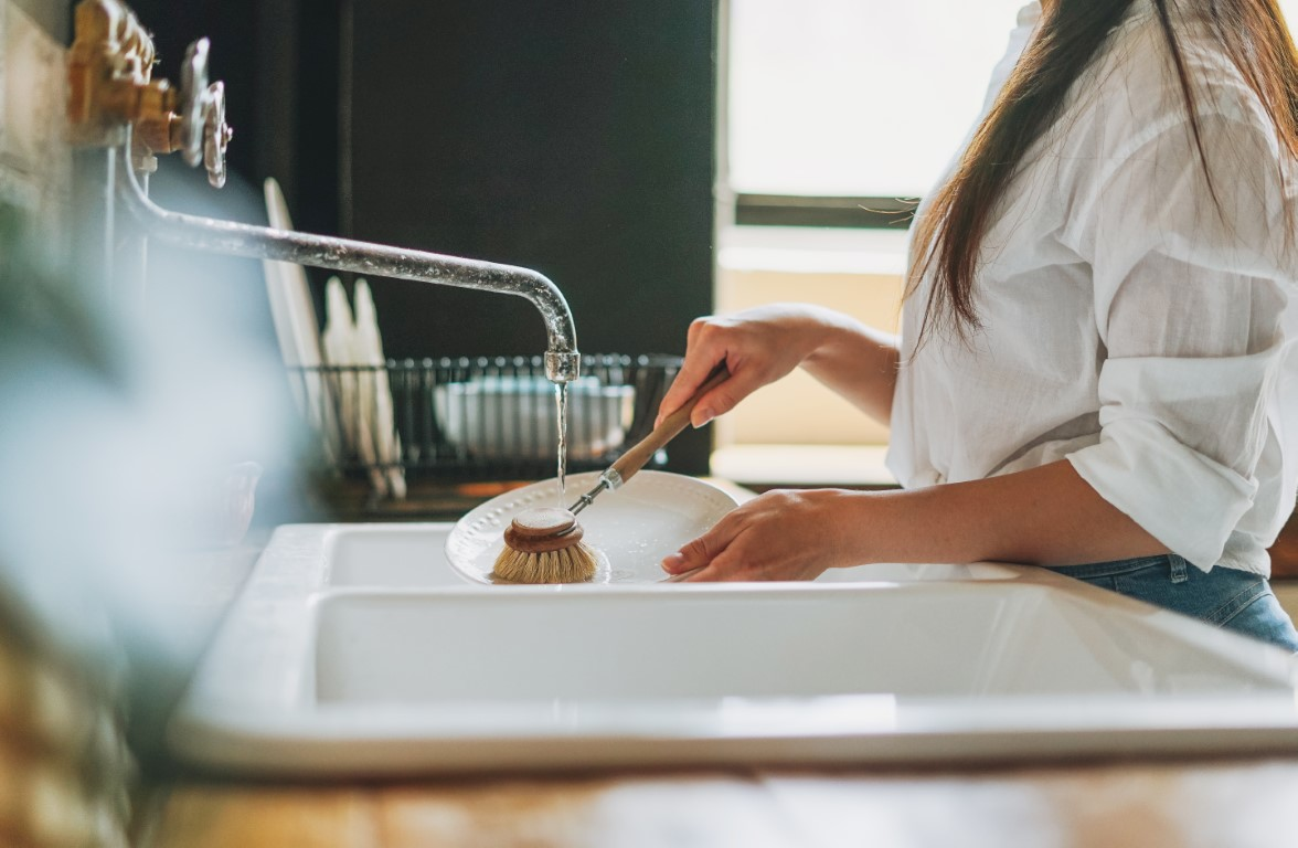 young-woman-washes-dishes-with-wooden-brush-with-n-4B585DJ