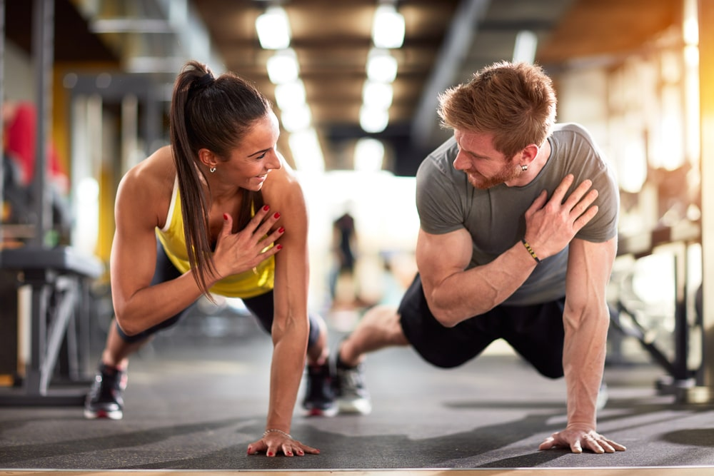 Man and woman workingout in a fitness centre arm training Fit-day