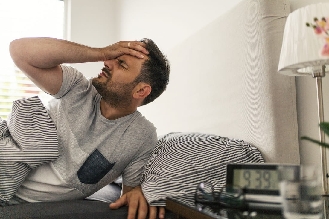 Muž chytající se za hlavu trpí bolestmi charakteristickými pro zbytkový alkohol v krvi