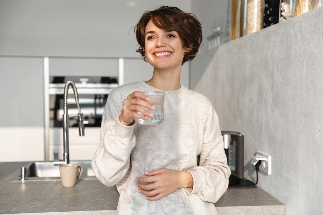 Žena popíjející vodu pro zrychlení metabolismu