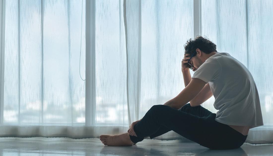 Muže sedící na zemi trápí posttraumatická stresová porucha