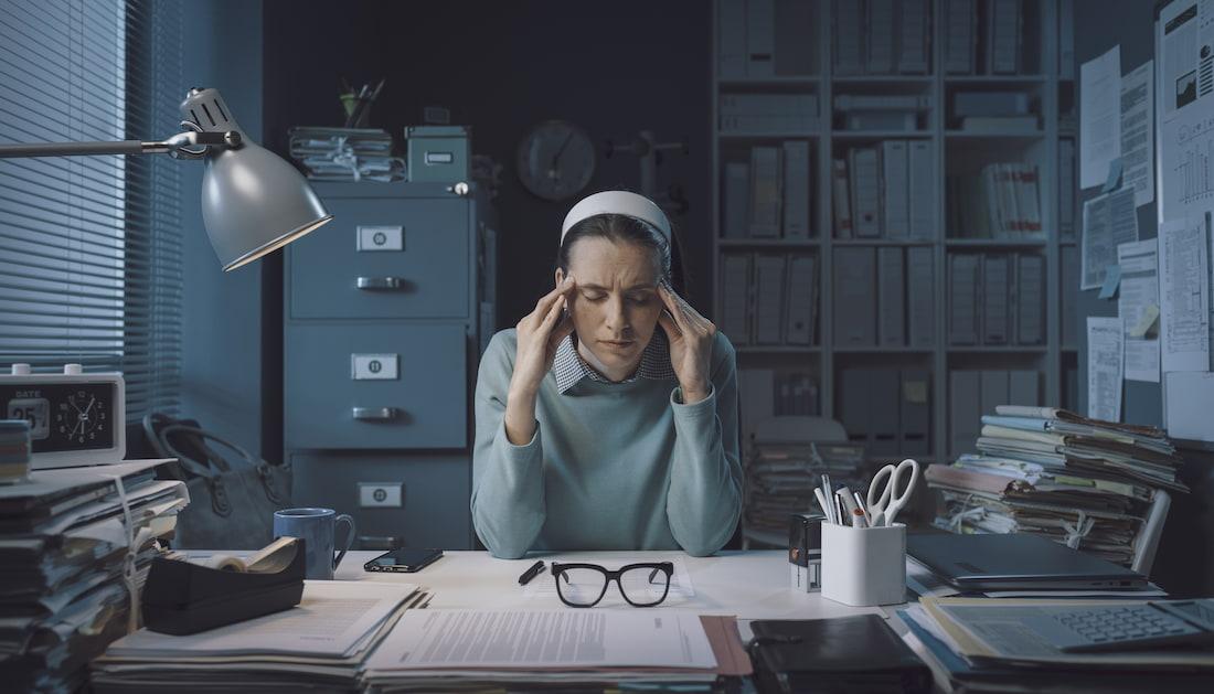 Ženu trápí bolest hlavy, což je jeden z příznaků, kterými se projevuje chronický stres