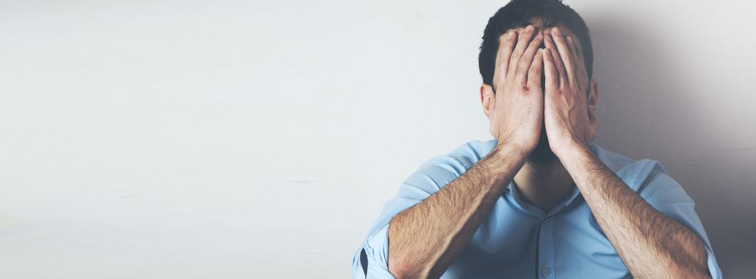 Muž svírající hlavu v dlaních prožívá úzkostné stavy