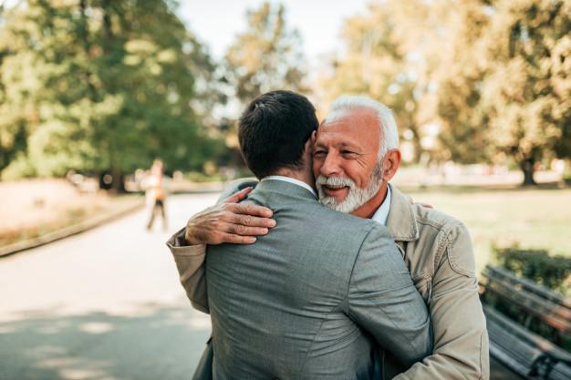 elderly-father-adult-son-hugging-park_109710-400