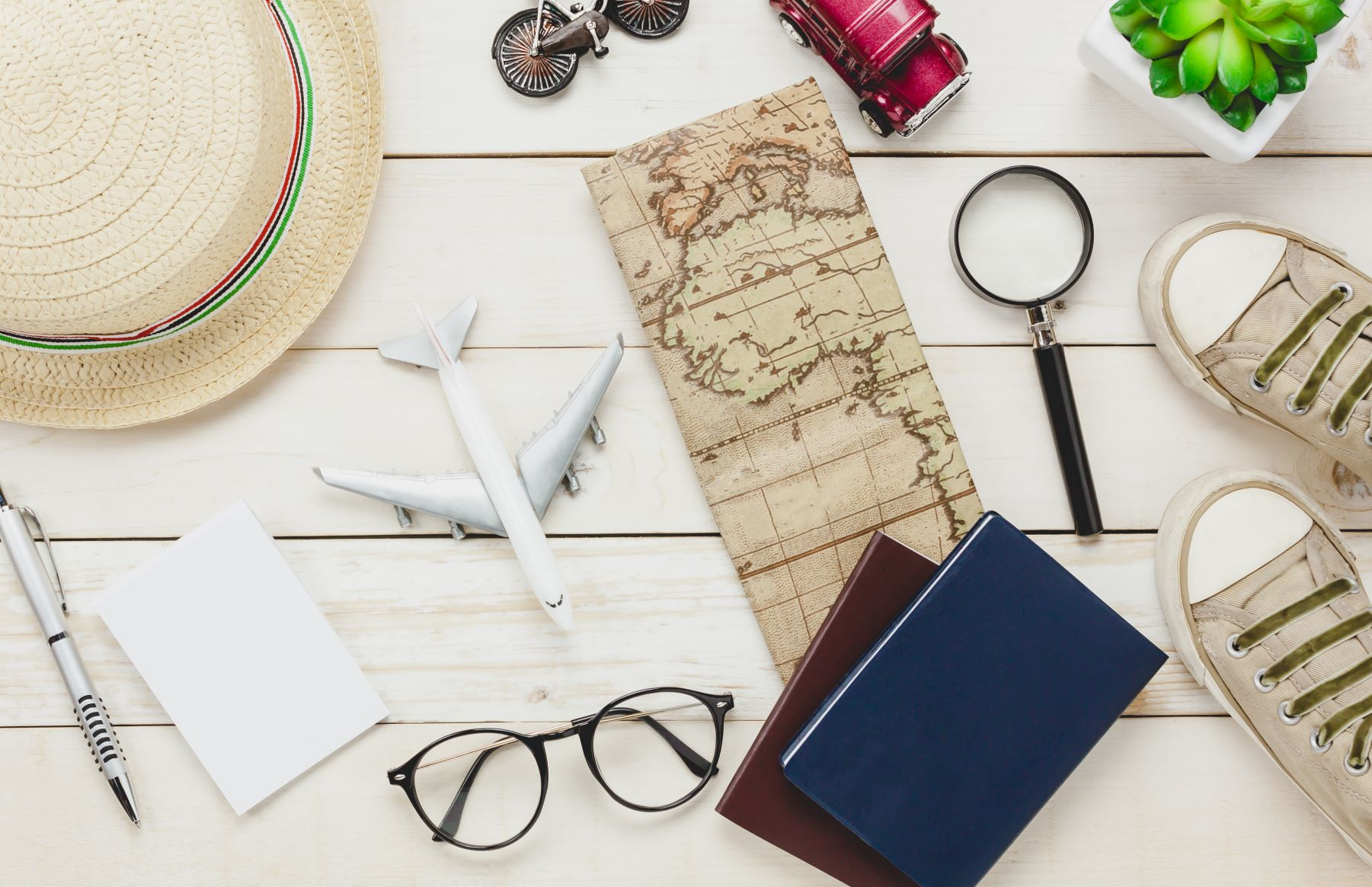 top-view-essential-travel-items-shoes-notebook-tree-map-pass