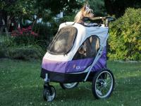 Kočárek pro psy s 38cm kolečky a nosností až 30 kg. Rozměry kabiny 72 × 45 × 60 cm, možnost připevnění upravovacího stolku. Barva fialovo-šedá. FOTO