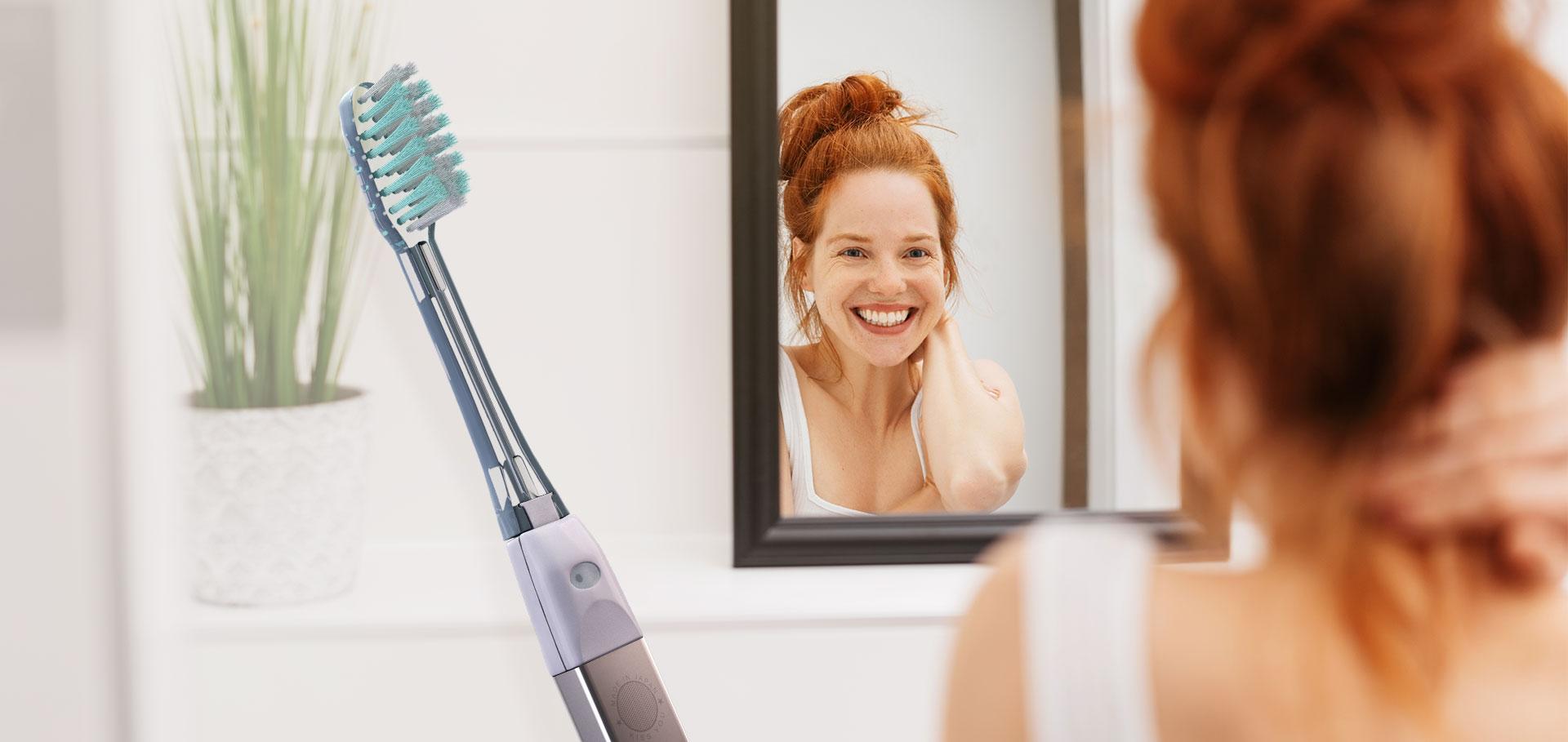 Manuální zubní kartáček IONICKISS ORIGINAL v koupelně se smějící se slečnou