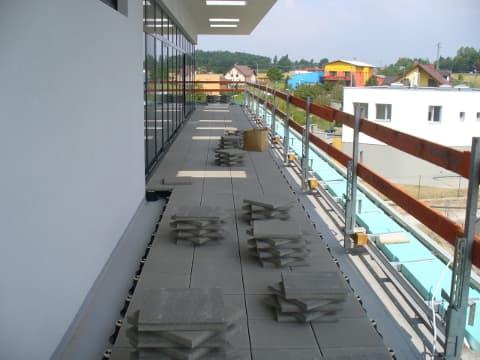 Využití terčů pod dlažbu na terasách v moderním bytovém domě.