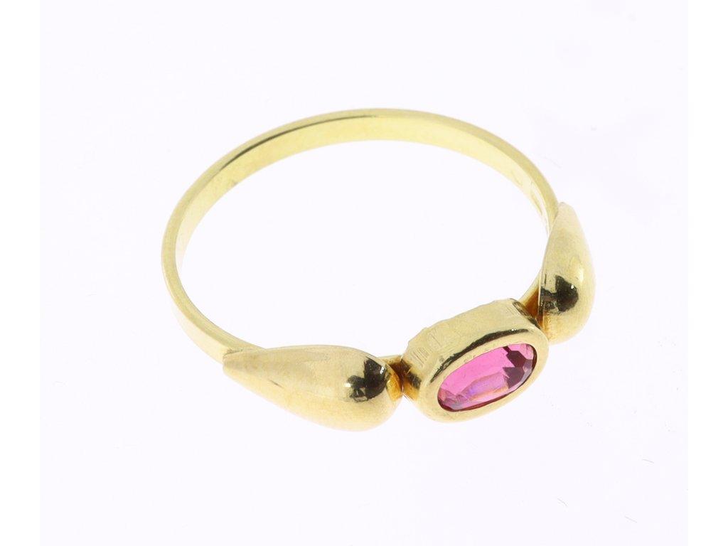 Zlatý prsten s červeným kamenem.