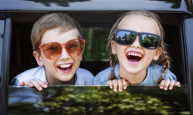 happy-kids-looking-out-car-window_53876-30797