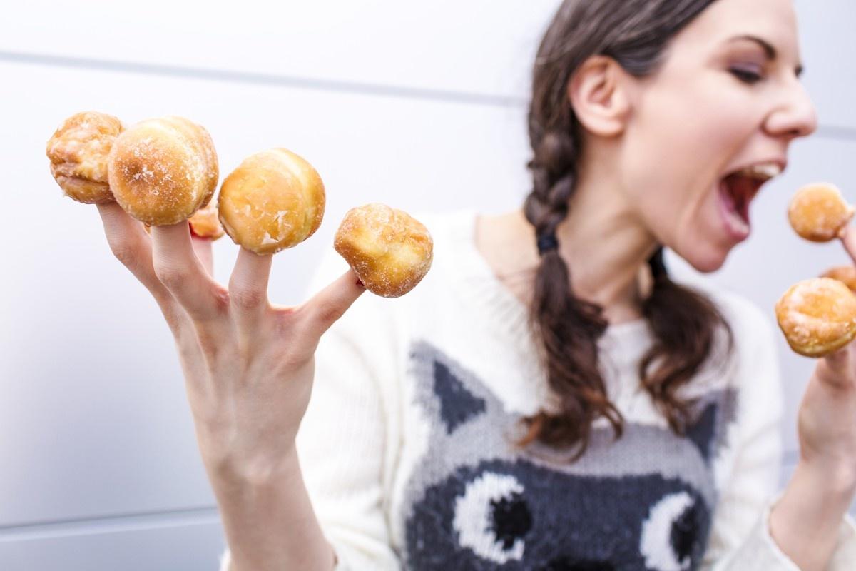 Žena a přejídání nezdravými jídly – koblihy