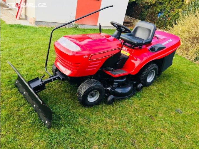 zahradní traktor husqvarna cth 180 červené barvy s radlicí vpředu na posekané zahradě