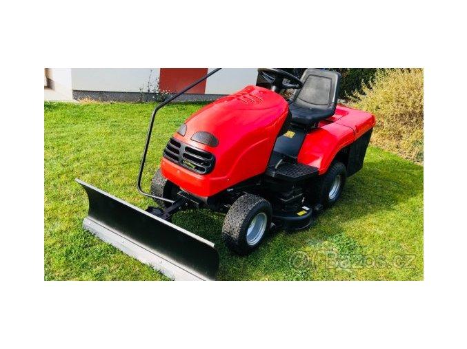 zahradní traktor starjet červené barvy s radlicí na trávníku