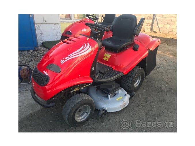 zahradní traktor starjet červené barvy před vraty