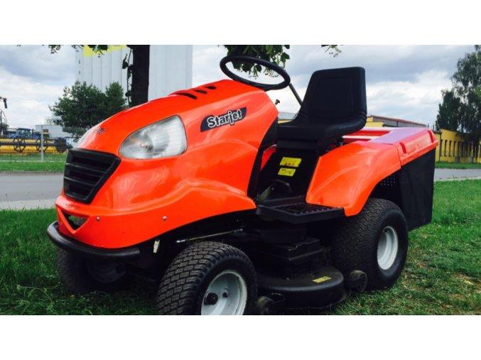zahradní traktor starjet oranžové barvy na trávníku u silnice