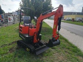 rypadlo, nakladač, minibagr mt 08 oranžové barvy na černých pásech před plachtou traktory kolín
