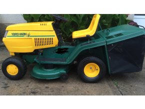 zahradní traktor yardman 20/102 zeleno-žluté barvy před keřem