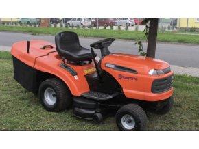 zahradní traktor husqvarna tc 139t oranžové barvy na trávě u silnice
