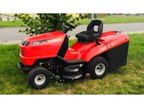 zahradní traktor honda 2216 červené barvy na posekané trávě u stromu