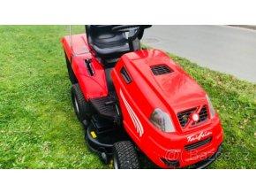 zahradní traktor starjet červené barvy a posekané zahradě u silnice