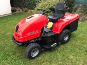 zahradní traktor starjet červené barvy na zahradě