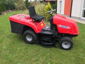 zahradní traktor starjet červené barvy na zahradě před domem
