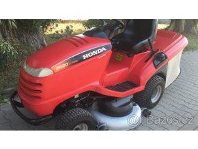 zahradní traktor honda 2622 červené barvy na chodníku před stromy