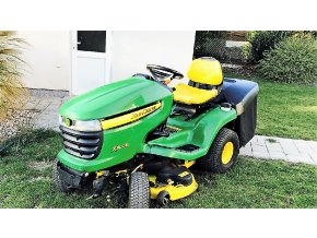 zahradní traktor john deere x300r zelené barvy na trávníku u domu