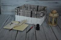 Jednoduchý bílý úložný boxík do skříňky, pleteno z novinově bílých ruliček, stříkáno bílou barvou, lakováno. Ušita látková košilka - novinový potisk