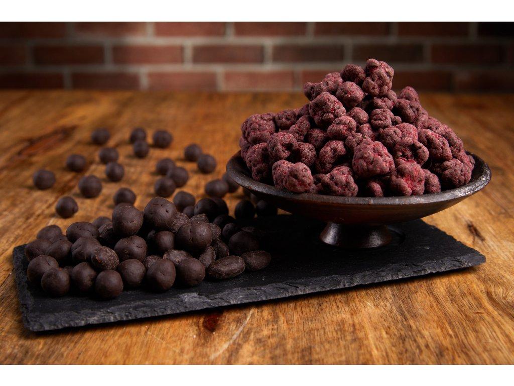 Lyofilizované maliny v jemné krustě z 72% hořké čokolády  a zaprášené malinovým prachem