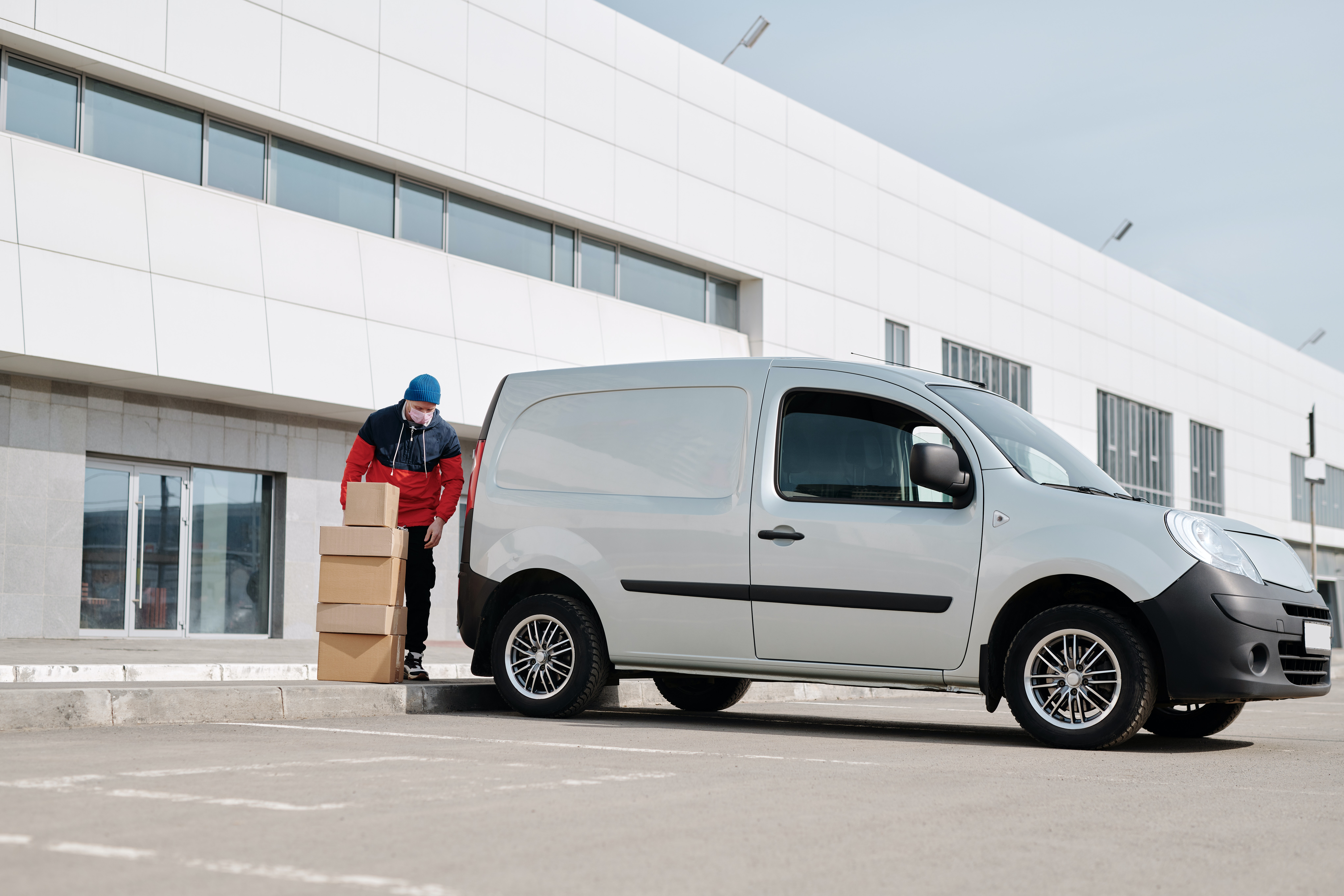 delivery-man-with-boxes-next-to-a-white-van-4391470_1